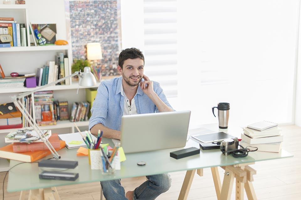 """alt=""""Mann sitzt vor Laptop in Arbeitszimmer"""" title=""""© jackfrog - Fotolia.com"""""""